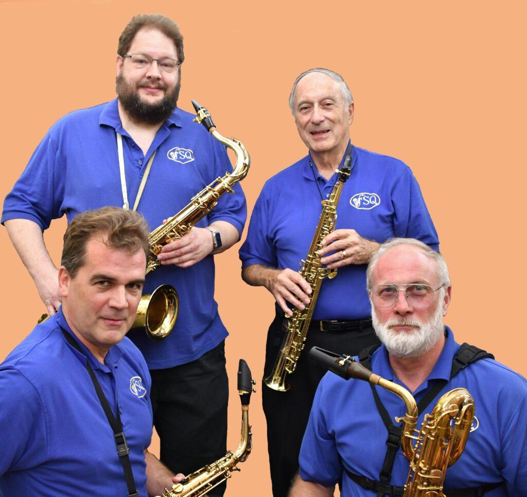Four men in blue shirts holding saxophones